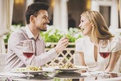 Datation de couples en restaurant et vin rouge potable Photos stock