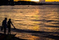 Datation douce de couples sur la plage pendant le coucher du soleil Images stock