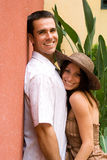 Date. A man and a woman standing at red wall, looking into camera, smiling royalty free stock photos