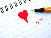 Date. A big red heart with pen drawn on white paper in a filofax with time Royalty Free Stock Images