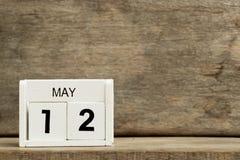 Date actuelle blanche 12 de calendrier de bloc et mois mai sur le fond en bois photo libre de droits