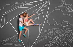 Date in the air. Happy valentines love story concept of a romantic couple on chalk drawings background. Couple on a date hang gliding over a countryside, female Royalty Free Stock Images