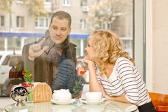 Date. Attractive young woman and her boyfriend. Date. Attractive young blond women and her boyfriend at small cafe. Guy with rose draws a heart on the glass Stock Image