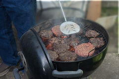 A Date For Backyard Food Making. A grill with hamburgers grilling in various stages of cooked Stock Images