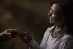 A date. Beautiful girl with a glass of red wine toasts with her date stock photos