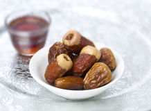 Date with black tea. A bowl of dates and two cups of black coffee at background Stock Images