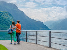 Date. Brunnen, Switzerland – Mai 30, 2015. Couple,  young woman and guy going on the road along the lake, hugging each other Royalty Free Stock Photography