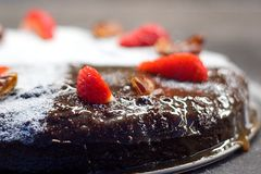 Date cake decorated with sugar, dry dates and fresh strawberries Stock Photos