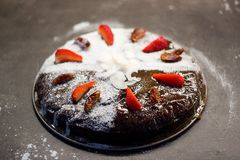 Date cake decorated with sugar, dry dates and fresh strawberries Royalty Free Stock Image