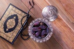 Date con il rosario e Corano santo sulla vista superiore del fondo di legno - Concetto del fitr di Al del Ramadan kareem/Eid immagini stock