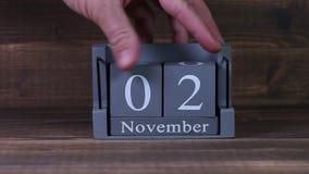 date 02 de établissement sur le calendrier en bois de cube pendant des mois de novembre clips vidéos