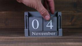 date 04 de établissement sur le calendrier en bois de cube pendant des mois de novembre banque de vidéos