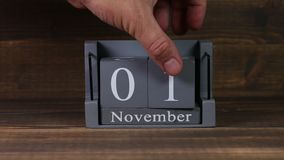 date 01 de établissement sur le calendrier en bois de cube pendant des mois de novembre banque de vidéos
