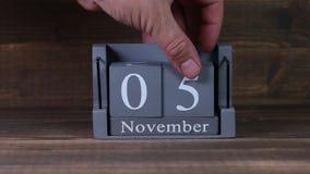 date 05 de établissement sur le calendrier en bois de cube pendant des mois de novembre banque de vidéos