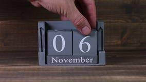 date 06 de établissement sur le calendrier en bois de cube pendant des mois de novembre banque de vidéos