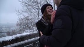 Date de jeunes couples en parc neigeux Le jeune homme et la belle fille marchent dehors banque de vidéos