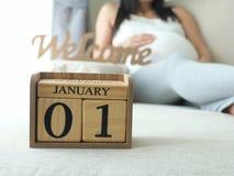 Date de nouvelle année d'échéance du ` s de bébé sur le calendrier avec le fond de femme enceinte Photographie stock libre de droits
