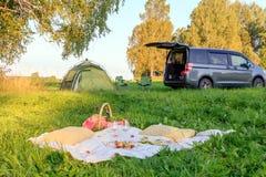 Date de pique-nique dans les chaises de forêt, de tente et de camp, minibus gris avec la porte ouverte, couverture, panier en osi photos stock