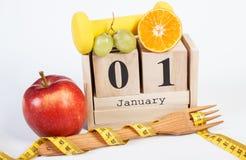 Date du 1er janvier sur le calendrier de cube, les fruits, les haltères et le ruban métrique, nouvelles années de résolutions Images libres de droits