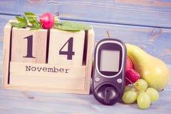 Date du 14 novembre, du glucometer et des fruits frais avec des légumes, concept de jour de diabète du monde Photographie stock libre de droits