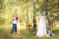 Date in the forest. A man leads a woman with closed eyes to a picnic site with a white cloth curtain tent. Guitar and bicycle with royalty free stock images