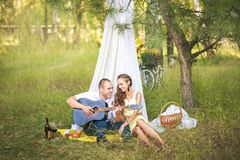 A man plays the beloved guitar. Man and woman in a hut, the concept of romance and idyll stock photos