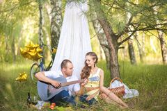 A man plays the beloved guitar. Man and woman in a hut, the concept of romance and idyll stock image