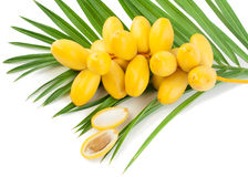 Date fruits. A bunch of fresh date fruits with palm leaf, one fruit is broken in half, the stone is visible on white background Stock Photos