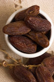 Date Fruits. In a white bowl on a wooden table Stock Photos