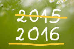 Date 2015 going to 2016 handwritten on real natural green background Stock Images
