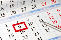 Date highlighted in red on calendar with black numbers next to the pen Stock Photo