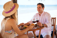 Date with his girlfriend at the beach. Young men enjoying a glass of wine and some food with his date at the beach royalty free stock images