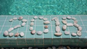 Date 2018 is laid out by pebble stones on the edge of the pool in the tropical resort stock video footage