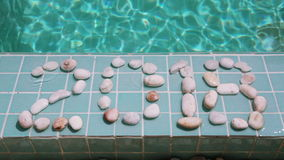 Date 2018 is laid out by pebble stones on the edge of the pool in the tropical resort stock footage