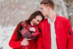 A date of lovers with my park in the winter. A bouquet of red flowers, walk, hug, kiss, laugh in a romantic setting. Portrait of a couple, husband and wife royalty free stock image