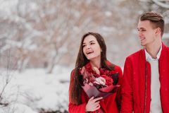 A date of lovers with my park in the winter. A bouquet of red flowers, walk, hug, kiss, laugh in a romantic setting. Portrait of a couple, husband and wife royalty free stock photo