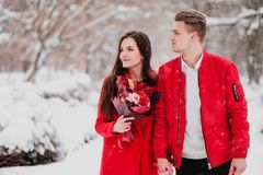 A date of lovers with my park in the winter. A bouquet of red flowers, walk, hug, kiss, laugh in a romantic setting. Portrait of a couple, husband and wife stock photos
