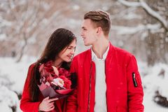A date of lovers with my park in the winter. A bouquet of red flowers, walk, hug, kiss, laugh in a romantic setting. Portrait of a couple, husband and wife royalty free stock images
