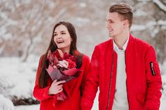 A date of lovers with my park in the winter. A bouquet of red flowers, walk, hug, kiss, laugh in a romantic setting. Portrait of a couple, husband and wife stock photography