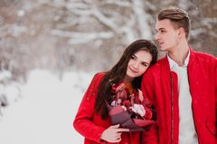 A date of lovers with my park in the winter. A bouquet of red flowers, walk, hug, kiss, laugh in a romantic setting. Portrait of a couple, husband and wife stock images