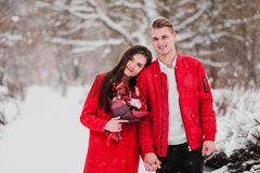 A date of lovers with my park in the winter. A bouquet of red flowers, walk, hug, kiss, laugh in a romantic setting. Portrait of a couple, husband and wife royalty free stock photography