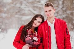 A date of lovers with my park in the winter. A bouquet of red flowers, walk, hug, kiss, laugh in a romantic setting