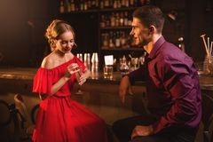 Woman in dress flirts with man in nightclub. Date in nightclub, attractive women in red dress flirts with men against bar counter in nightclub. Love relationship Stock Image