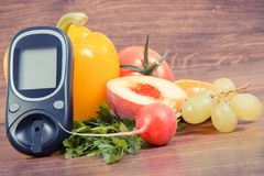 Date 14 November as symbol of world diabetes day, glucometer for measuring sugar level and fruits with vegetables Stock Photos