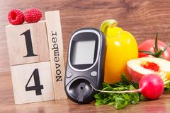 Date 14 November as symbol of world diabetes day, glucose meter for measuring sugar level and fruits with vegetables Stock Photo