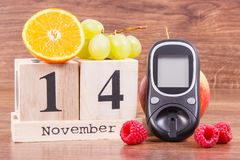 Date of 14 November, glucose meter and ripe fruits, world diabetes day concept Stock Photography