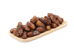 Date palm dried fruit. In wooden plate isolated on white background with clipping path stock image