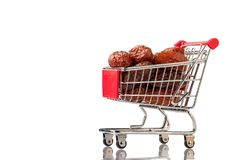Date palm fruits in a shopping cart,  on a white background. Place for text. Isolate stock photo