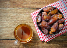 Date-palm in wood bowl with cup of tea on wood Royalty Free Stock Image