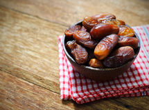 Date-palm in wood bowl with cup of tea on wood Royalty Free Stock Photography